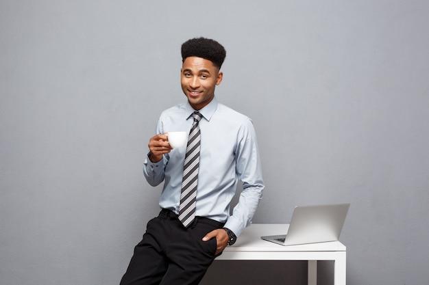 Concept d'entreprise - portrait d'homme d'affaires afro-américain ayant un café assis à un bureau à l'aide d'un ordinateur portable.