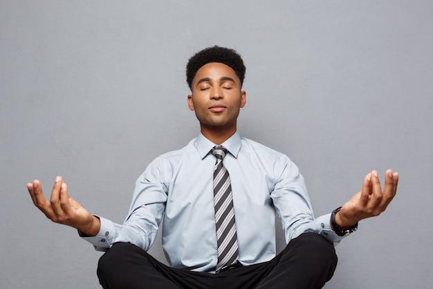 Concept d'entreprise - portrait d'homme d'affaires afro-américain faisant de la méditation et du yoga avant de travailler.
