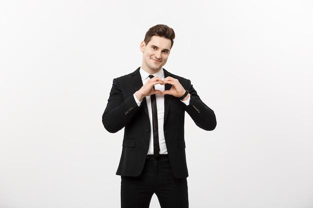 Concept d'entreprise : portrait d'un homme d'affaires séduisant et charmant tenant la main dans le geste du cœur et levant les sourcils tout en souriant, isolé sur fond gris blanc.