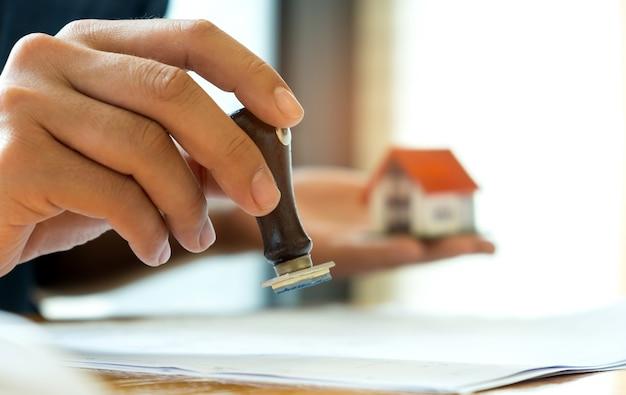 Concept d'entreprise de prêt hypothécaire, close-up rubber stamp et maison modèle en main.