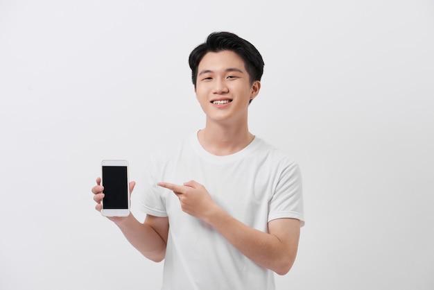 Concept d'entreprise, de réussite et de technologie avec un homme d'affaires montrant un smartphone avec un écran vide et un espace de copie isolé sur blanc.