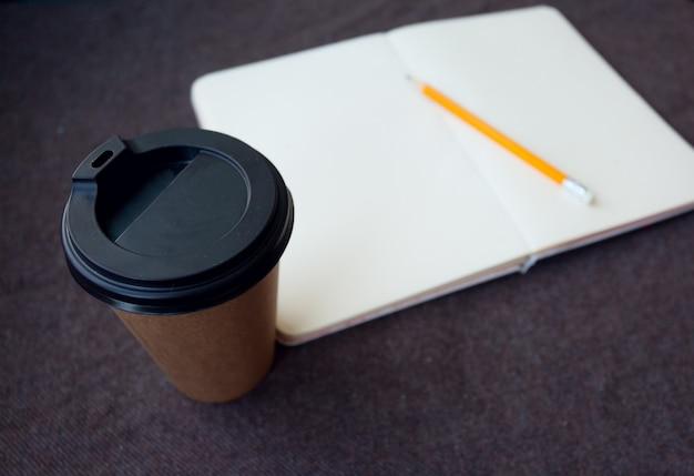 Concept d'entreprise, de style de vie, de nourriture et de café -crayon, cahier et tasse de café en papier sur fond de tissu marron