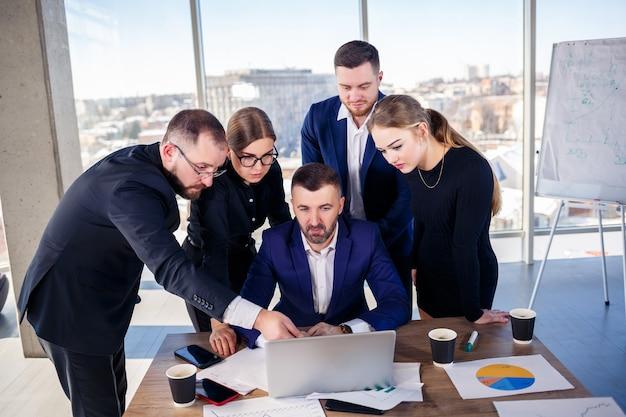 Concept d'entreprise, de technologie et de bureau - équipe commerciale heureuse avec des ordinateurs portables, des documents et du café. réunion avant le début de la journée de travail pour discuter d'un plan d'affaires