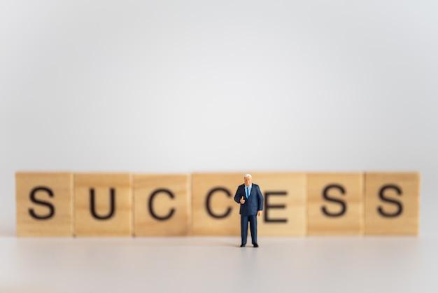 Concept d'entreprise et de travail. homme d'affaires figure miniature personnes debout avec montrer le pouce vers le haut avec un texte de bloc de lettre en bois succès.