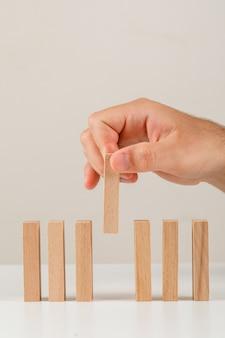 Concept d'entreprise sur la vue latérale du fond blanc. main plaçant un bloc de bois en ligne.