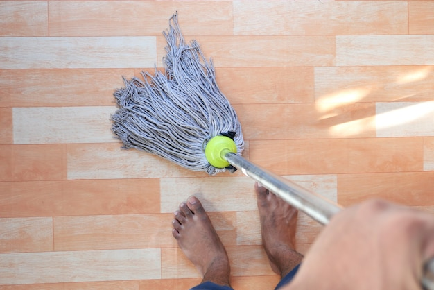 Concept d'entretien ménager à domicile nettoyage de parquet avec une vadrouille