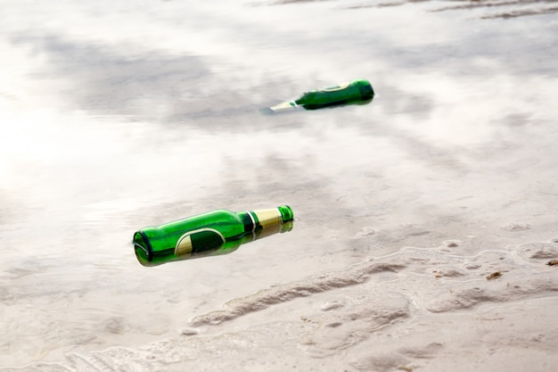 Concept d'enveloppement, bouteille de bière verte vide sur la plage.