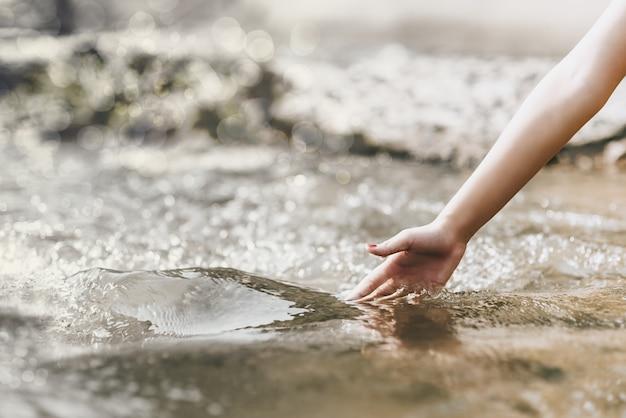 Concept de l'environnement, toucher naturel, main touche l'eau dans la nature