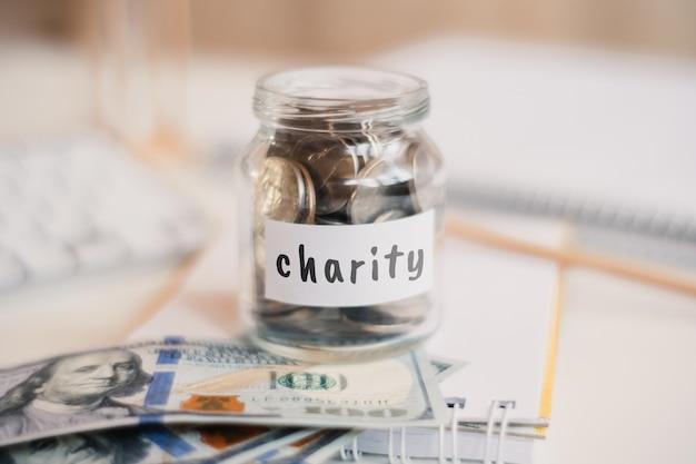 Concept d'épargne caritative - pot en verre avec pièces et inscription.