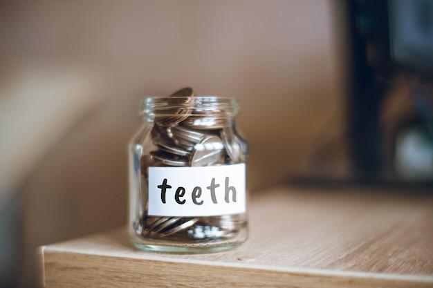 Concept d'épargne dents - pot en verre avec pièces et inscription.