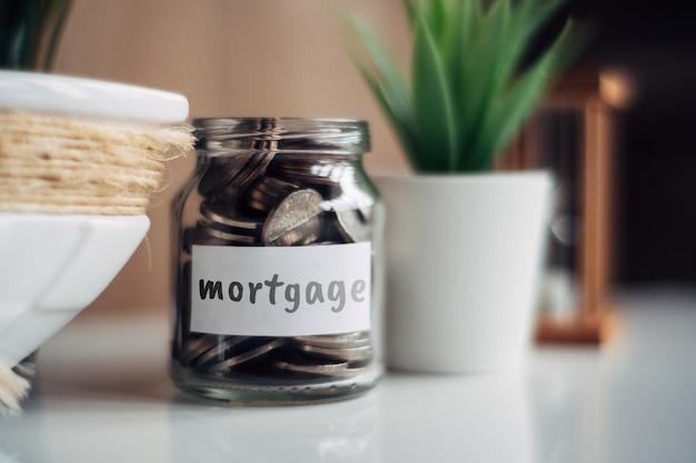 Concept d'épargne hypothécaire - bocal en verre avec pièces et inscription.