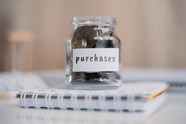 Concept d'épargne pour les achats - pot en verre avec pièces et inscription.