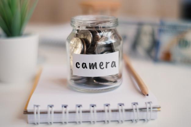 Concept d'épargne pour appareil photo - pot en verre avec pièces et inscription.
