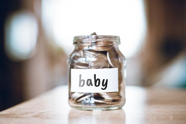 Concept d'épargne pour bébé - bocal en verre avec pièces et inscription.