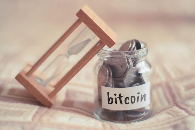 Concept d'épargne pour bitcoin - pot en verre avec pièces et inscription.