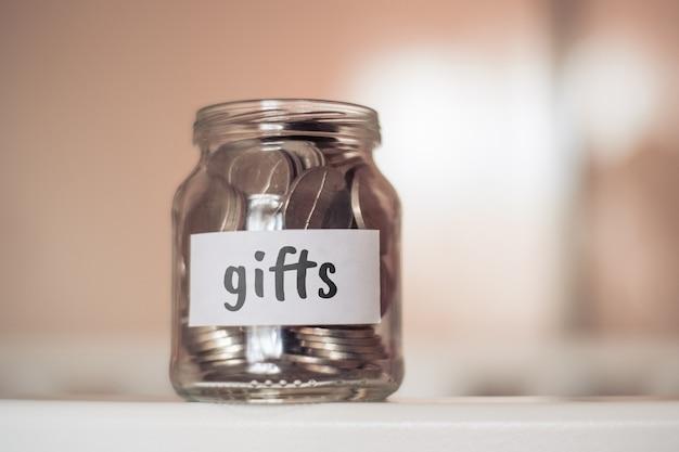 Concept d'épargne pour les cadeaux - bocal en verre avec pièces et inscription.