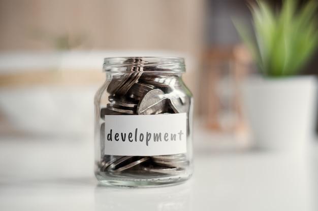 Concept d'épargne pour le développement - pot en verre avec pièces et inscription.