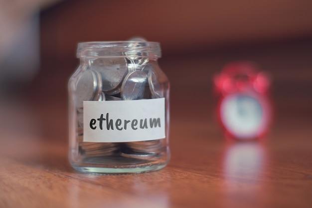 Concept d'épargne pour ethereum - pot en verre avec pièces et inscription.