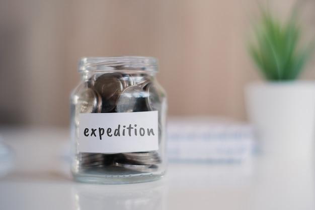 Concept d'épargne pour l'expédition - bocal en verre avec pièces et inscription.