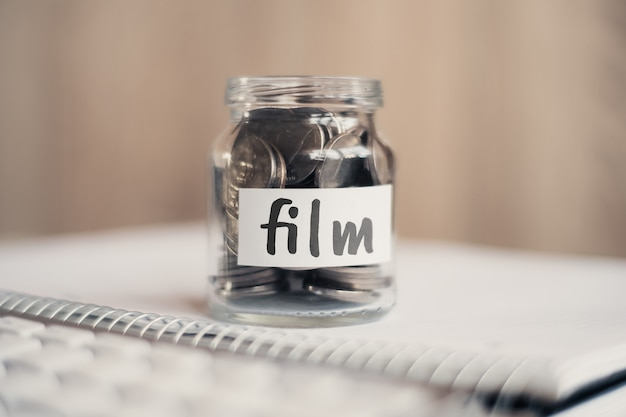Concept d'épargne pour le film - pot en verre avec pièces et inscription.