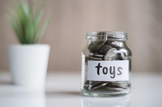 Concept d'épargne pour jouets - pot en verre avec pièces et inscription.