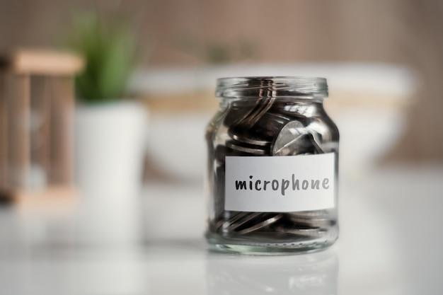 Concept d'épargne pour microphone - bocal en verre avec pièces et inscription.