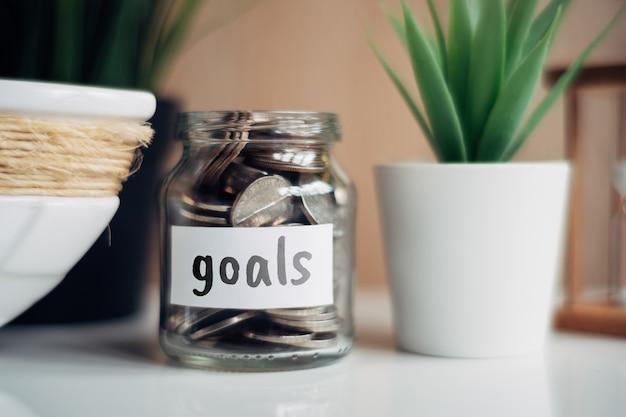 Concept d'épargne pour les objectifs - pot en verre avec pièces et inscription.