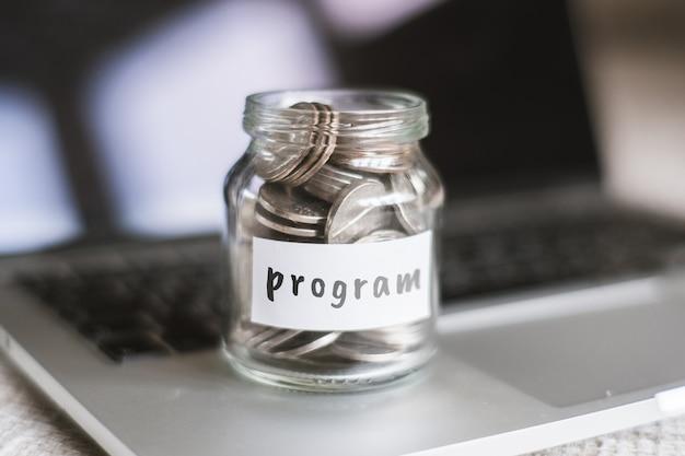 Concept d'épargne pour le programme - pot en verre avec pièces et inscription.