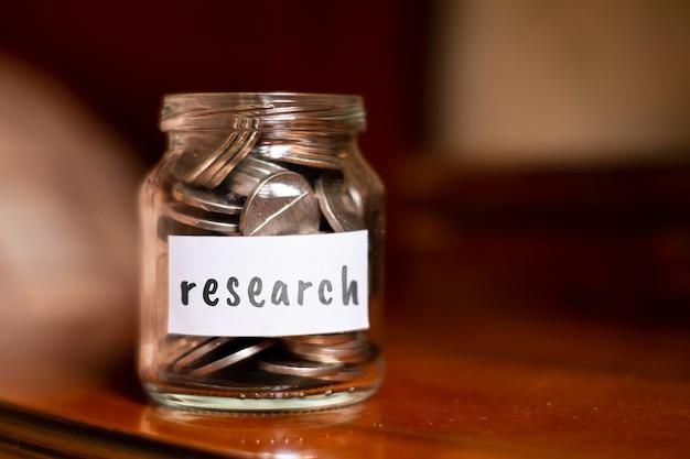 Concept d'épargne pour la recherche - pot en verre avec pièces et inscription.