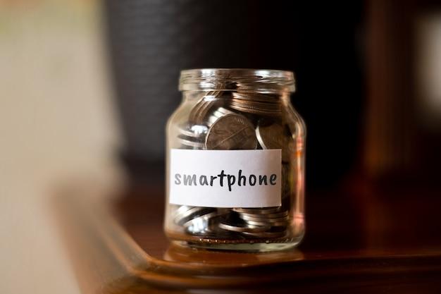 Concept d'épargne pour smartphone - bocal en verre avec pièces et inscription.