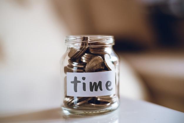Concept d'épargne pour le temps - pot en verre avec pièces et inscription.