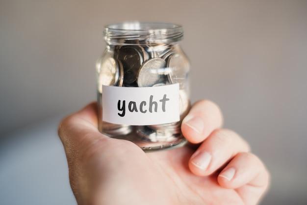 Concept d'épargne pour yacht - bocal en verre avec pièces et inscription.