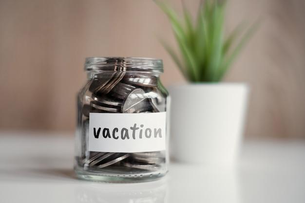 Concept d'épargne vacances - bocal en verre avec pièces et inscription.