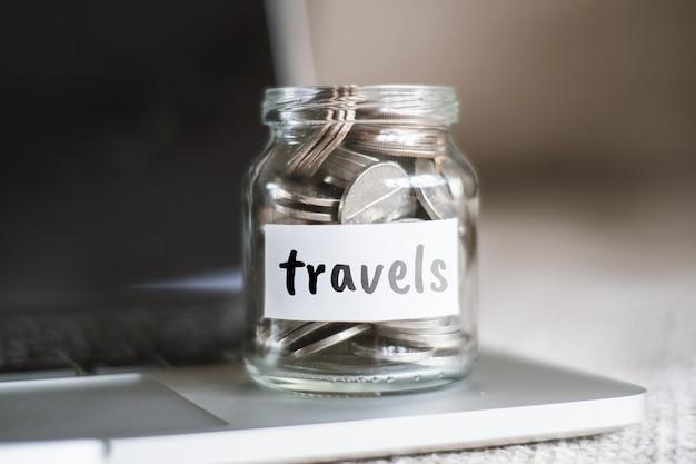 Concept d'épargne de voyages - pot en verre avec pièces et inscription.