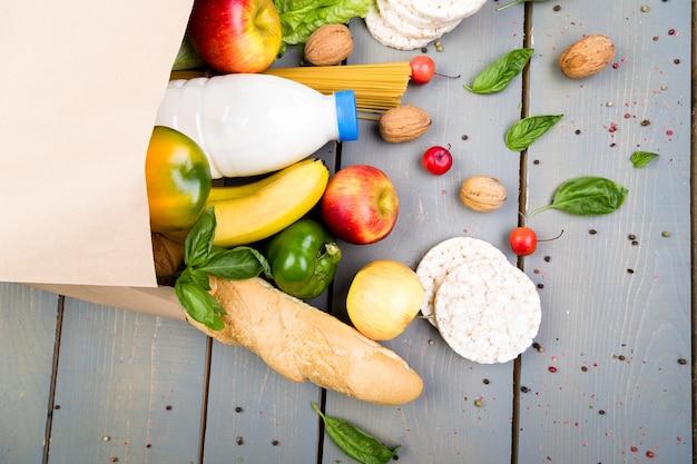 Concept d'épicerie. différents aliments dans un sac en papier sur bois. mise à plat.