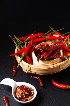 Concept d'épices alimentaires assortiment de piments dans un plateau en bambou en osier sur une planche en pierre d'ardoise noire avec espace de copie