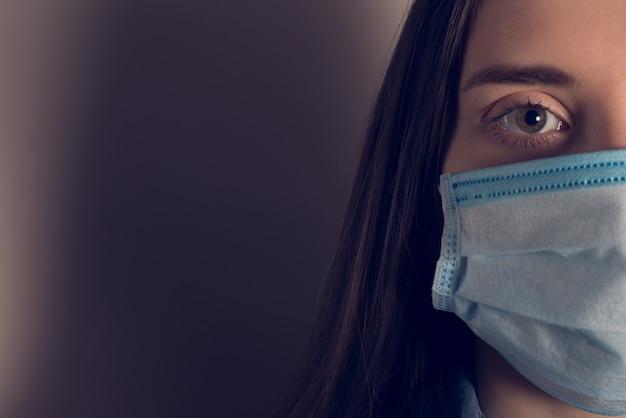 Concept d'épidémie 2019-ncov. recadrée en gros plan photo portrait de terrifié effrayé se sentir mal humain portant un masque facial isolé mur gris foncé avec une place vide pour le texte