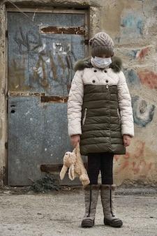 Concept d'épidémie et de quarantaine - une fille avec un masque facial et une peluche seule dans la rue de la ville