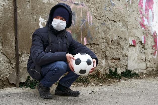 Concept d'épidémie et de quarantaine - un garçon avec un masque facial et un ballon seul dans la rue de la ville