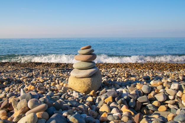 Le concept d'équilibre et d'harmonie. pierres sur la plage dans la nature. une pyramide de pierres sur une plage de galets, en arrière-plan un arrière-plan flou de la mer et du ciel à l'aube