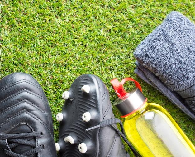 Concept d'équipement de sport, spike de football, serviette et bouteille de boisson énergétique sur l'herbe