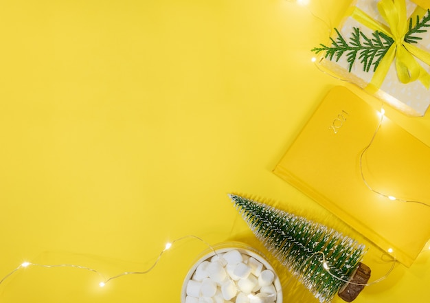 Concept d'espace de travail de noël en couleur jaune. cadre de bloc-notes-organisateur sur 2021, petit arbre de noël, coffret cadeau diy, tasse de cacao avec des guimauves, lumières de noël. planification. vue de dessus, mise à plat. copiez l'espace.