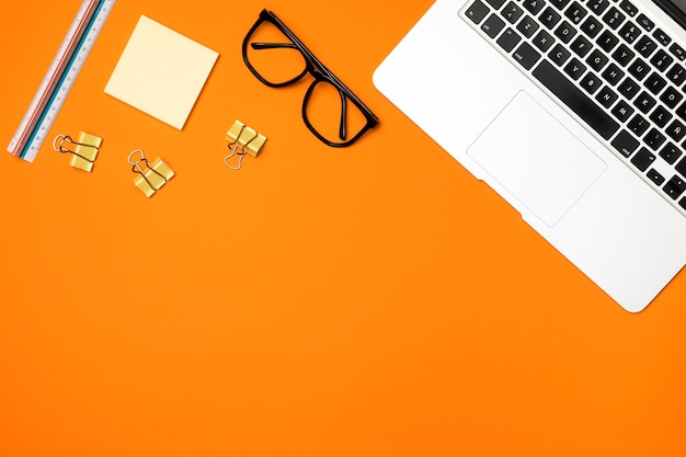 Concept d'espace de travail plat laïque avec fond orange