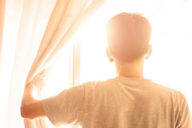 Concept d'espoir. homme ouvrir le rideau voir le lever du soleil