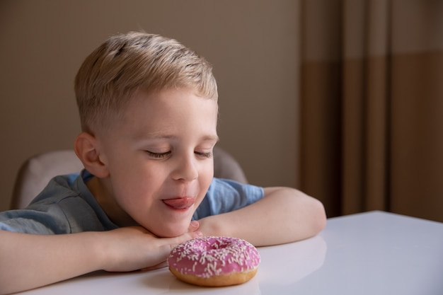 Le concept est la nourriture inutile. un petit garçon aux cheveux blonds mange un beignet rose à la maison. il est content, il aime le beignet.