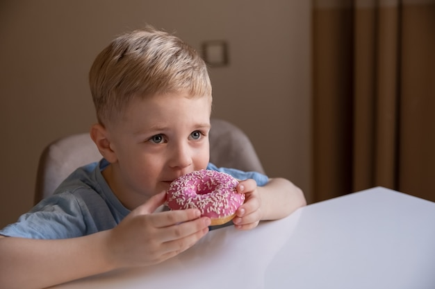 Le concept est de la nourriture inutile un petit garçon aux cheveux blonds mange un beignet rose à la maison il est heureux qu'il aime le beignet