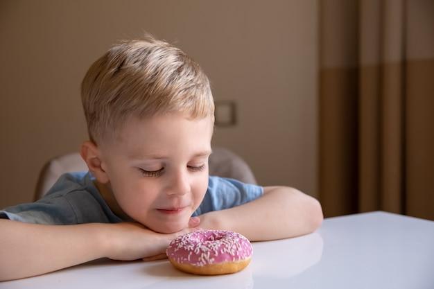 Le concept est de la nourriture inutile un petit garçon aux cheveux blonds mange un beignet rose à la maison il est heureux