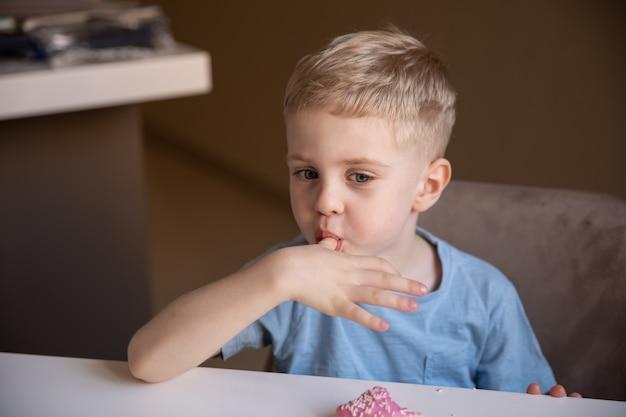 Le concept est la nourriture inutile. un petit garçon aux cheveux blonds mange un beignet rose à la maison et se lèche les doigts. il aime le beignet.