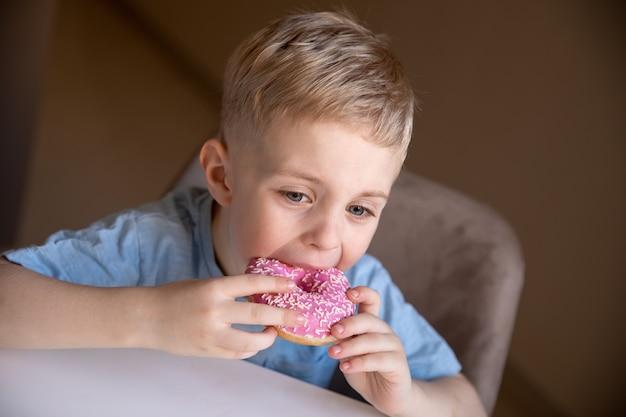 Le concept est de la nourriture inutile un petit garçon aux cheveux blonds mange un beignet rose à la maison