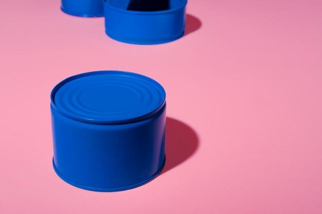 Concept esthétique avec boîte de conserve peinte en bleu sur rose